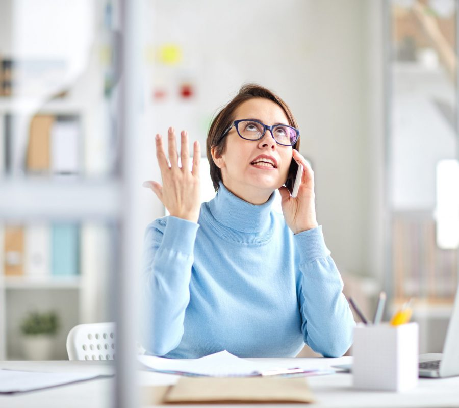 Annoyed office manager explaoinign something to client on the phone while sitting by desk in office