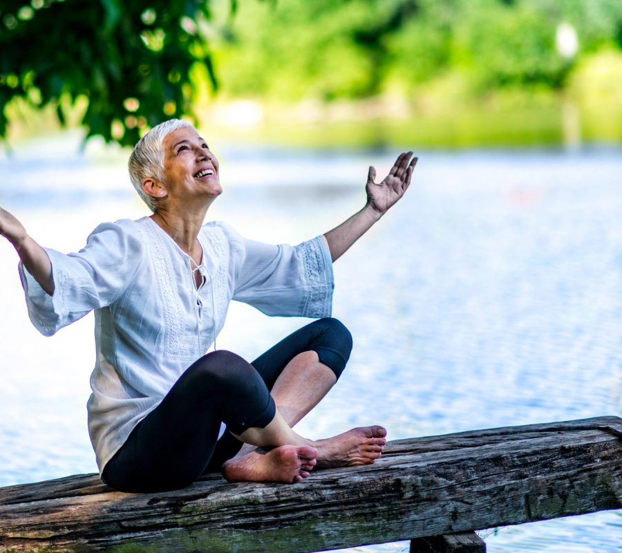 Beautiful, mindful, mature woman sitting by the water, enjoying peace and tranquility of the nature