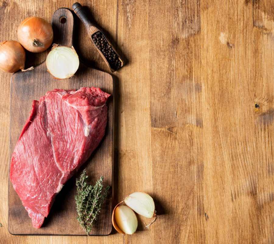Raw red meat of beef with spices on cutting board. Copy space available.