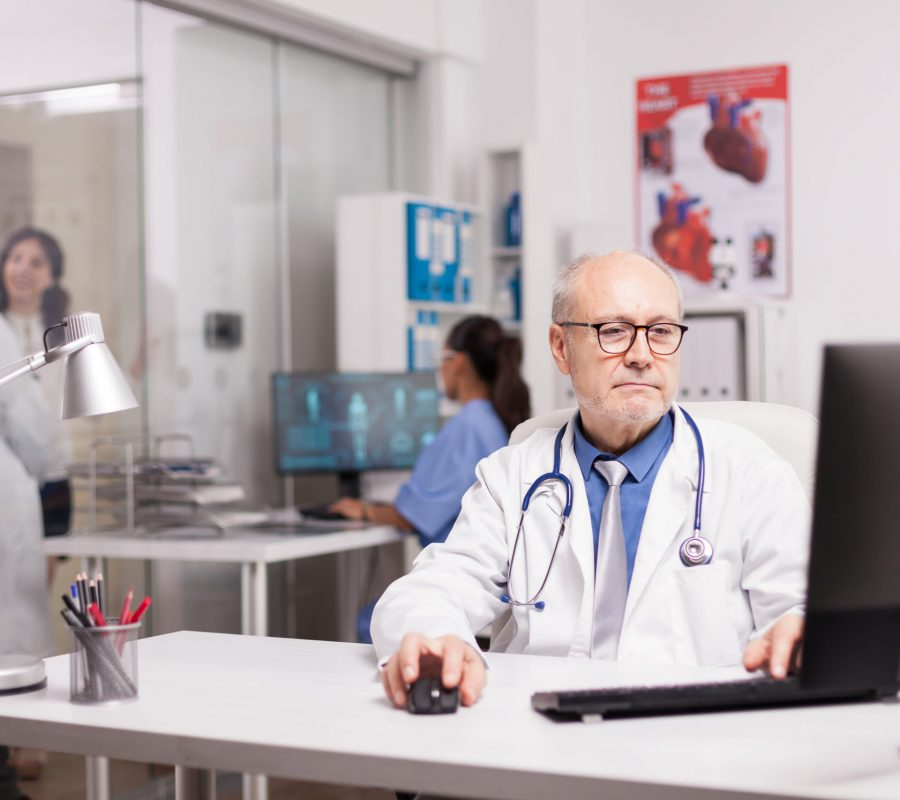 Senior specialist physician writing science report on computer in private clinic while his young colleague is looking at patient in hospital corridor wearing white coat.