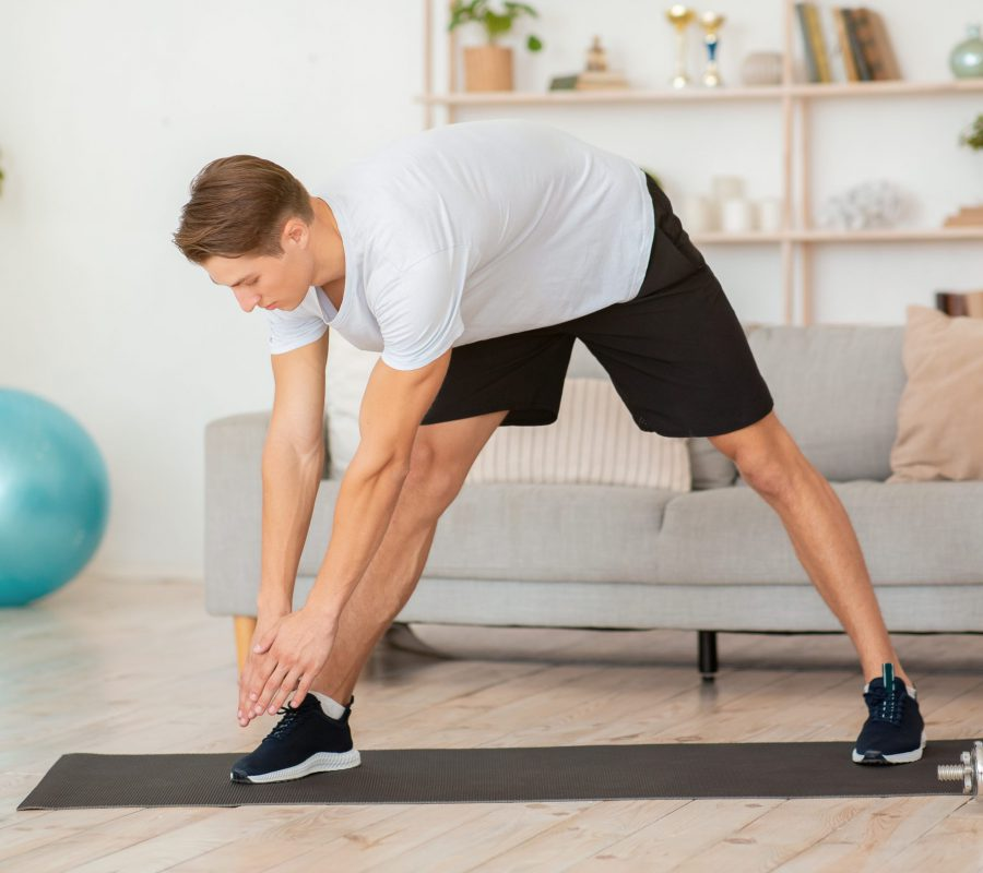 Warm up and stretch in workout. Muscular guy incline and stretching in living room interior with sports equipment, free space